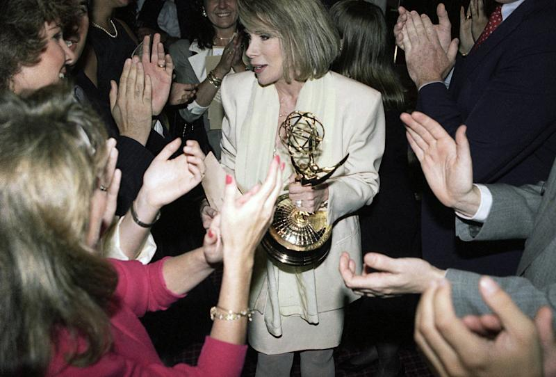 Talk show host Joan Rivers is applauded by fans after winning her first Emmy as best talk show host on June 28, 1990. (AP Photo/Marty Lederhandler)