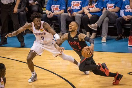 Apr 21, 2019; Oklahoma City, OK, USA; Portland Trail Blazers guard Damian Lillard (0) dribbles while Oklahoma City Thunder forward Jerami Grant (9) grabs his arm during the second half in game four of the first round of the 2019 NBA Playoffs at Chesapeake Energy Arena. Mandatory Credit: Rob Ferguson-USA TODAY Sports
