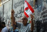 A man carries a flag and a noose during a demonstration in Beirut