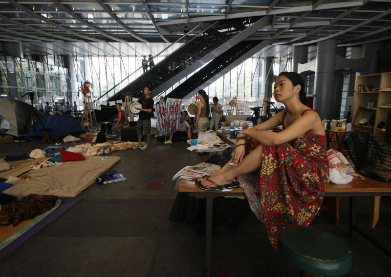 A protester sits on a table as bailiffs evict Hong Kong's Occupy activists from a public space underneath HSBC's Asian headquarters Tuesday, Sept. 11, 2012. The protesters had ignored a court order requiring them to leave the site by Aug. 27. (AP Photo/Kin Cheung)