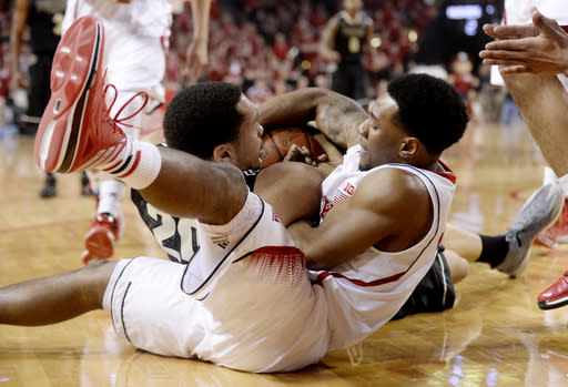 Purdue center A. J. Hammons, left, and Nebraska guard Benny Parker, right, battle over a loose ball during the first half of an NCAA college basketball game in Lincoln, Neb., Sunday, Feb. 23, 2014. (AP Photo/Francis Gardler)