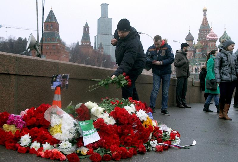 Russian mourners lay flowers at the site when opposition leader Boris Nemtsov was shot dead near Saint-Basil's Cathedral in Moscow, on February 28, 2015