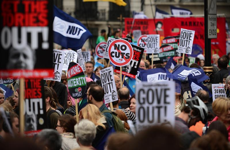 People hold banners and placards as they take part in a march and rally in central London on July 10, 2014 (AFP Photo/Carl Court)