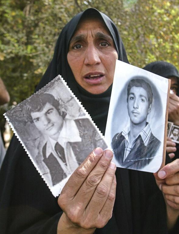 An Iraqi woman shows in this May 2003 picture photographs of her two sons who were believed to have been killed during Saddam's rule
