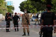 Army soldier and police officers guard a cordoned-off street leading to the site of a passenger plane crash in a residential area near an airport in Karachi,