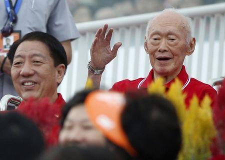 Former PM Lee waves to audience during Singapore's 49th National Day Parade at floating platform in Marina Bay