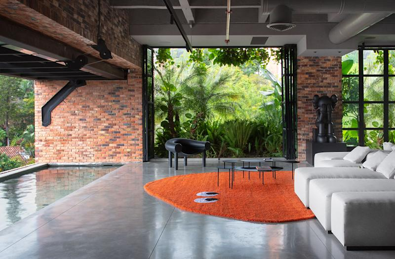 Pool-friendly Sunbrella fabric covers the massive sofa in the primary social space, presided over by another KAWS sculpture. Konstantin Grcic chair by Magis; custom rug by Gres.