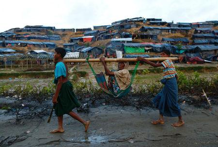 Rohingya refugee children carry an old woman in a sling near Balukhali makeshift refugee camp in Cox's Bazar, Bangladesh, September 13, 2017. REUTERS/Danish Siddiqui