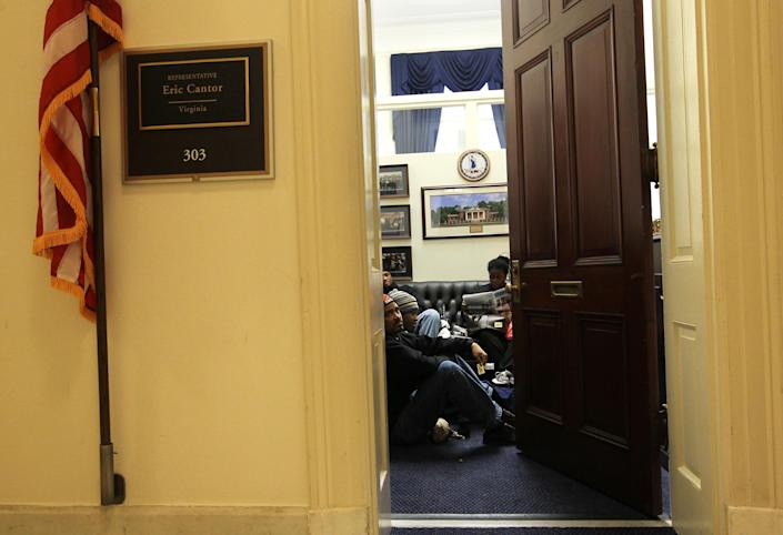 """WASHINGTON, DC - DECEMBER 06: Activists wait in U.S. House Majority Leader Rep. Eric Cantor's (R-VA) office for an unscheduled meeting with the congressman December 6, 2011 on Capitol Hill in Washington, DC. Activists from across the nation visited congressional offices as they participated in the """"Take Back the Capitol"""" action to ask legislators to create more jobs and take care of the """"99 percent."""" (Photo by Alex Wong/Getty Images)"""