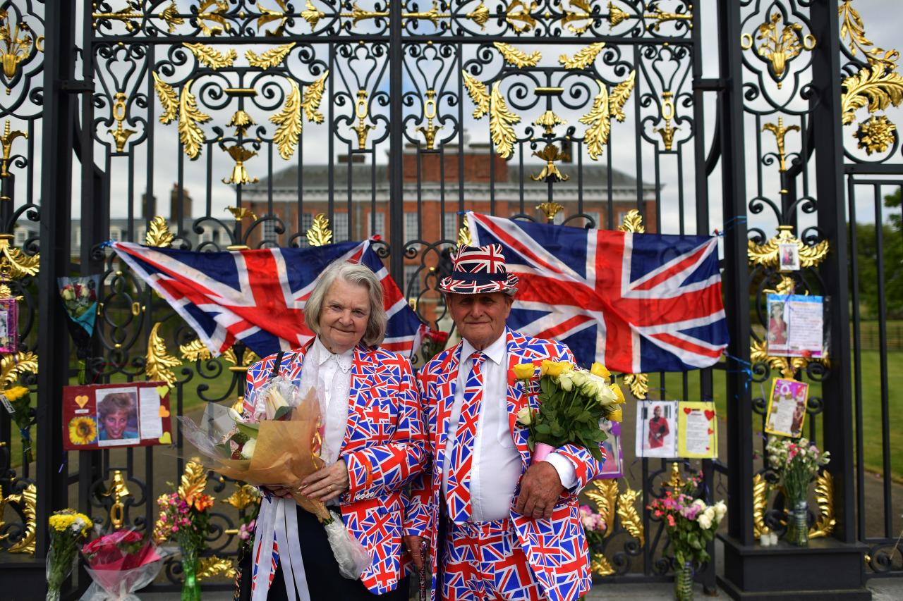 <p>Royal supporters pose in front of tributes to Princess Diana on the gate of Kensington Palace in London, England. Flowers, flags and tributes were laid at the gate of Diana's former home of Kensington Palace to mark the 19th anniversary of her death. (Carl Court/Getty Images)<br /></p>