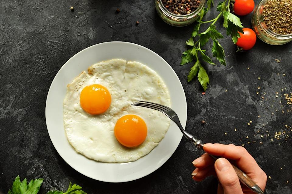 person eating two eggs off a white plate