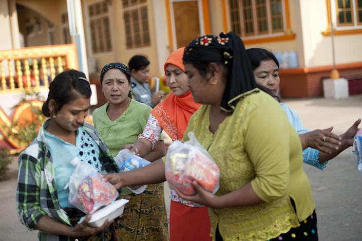 People donate food to residents who fled from conflict areas near the Myanmar-China border as they arrive at a temporary refugee camp at a monastery in Lashio, northern Myanmar, on February 18, 2015 (AFP Photo/Ye Aung Thu)