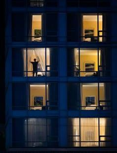 Outline of a person in one of several lit hotel windows, closing the curtains.
