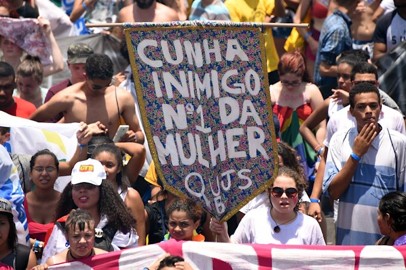 "Students hold a sign which reads ""Cunha enemy no.1 of woman"" against the President of the Chamber of Deputies Eduardo Cunha in Brasilia on November 13, 2015 (AFP Photo/Evaristo Sa)"