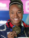 File-This July 28, 2019, file photo shows United States gold medalist Simone Manuel posing with her medal following the women's 50m freestyle final at the World Swimming Championships in Gwangju, South Korea. Katie Ledecky is among several big names diving back in with three months to go until the U.S. Olympic trials. Caeleb Dressel, Manuel, double backstroke world-record holder Regan Smith, and Ryan Lochte will swim over four days in the first single-site American meet since the pandemic began. (AP Photo/Lee Jin-man)