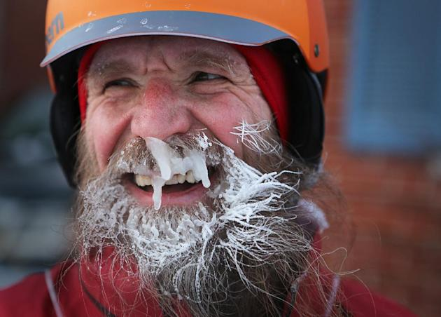"In a Feb.19, 2014 photo, Fraser Cunningham, 56, a General Electric engineer, arrives home in Madeira, Ohio, with ice that has formed on his beard, which is a product of freezing water vapors produced from breathing. Cunningham calls it his ""chinsulation."" Cunningham hasn't missed a day biking to and from work for a year and a half. (AP Photo/The Cincinnati Enquirer, Carrie Cochran) MANDATORY CREDIT; NO SALES"