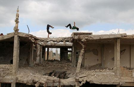 Parkour coach Ibrahim al-Kadiri (R), 19, and Muhannad al-Kadiri, 18, demonstrate their Parkour skills amid damaged buildings in the rebel-held city of Inkhil, west of Deraa, Syria, April 7, 2017. Ibrahim discovered Parkour in Jordan, where he had fled to escape the war. Back in his home town since 2015, he now leads a group of 15 practitioners. REUTERS/Alaa Al-Faqir