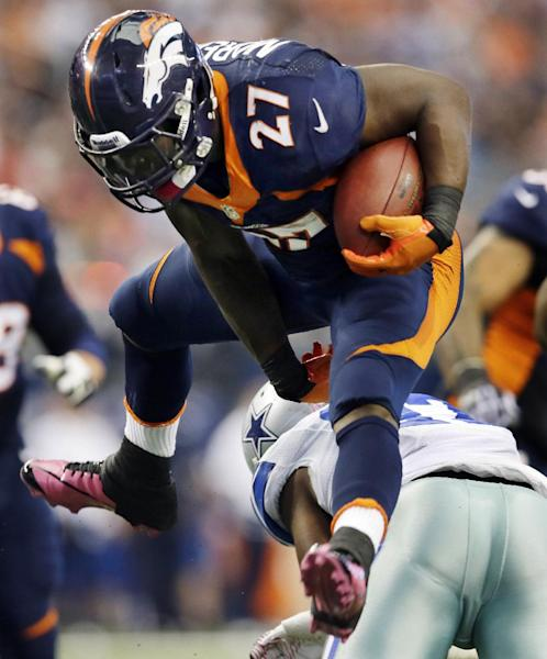 Denver Broncos running back Knowshon Moreno (27) hurdles J.J. Wilcox during the second quarter of an NFL football game Sunday, Oct. 6, 2013, in Arlington, Texas. (AP Photo/Tony Gutierrez)