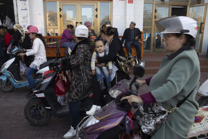 US Uighur residents past on bikes in Hotan in western China's Xinjiang region, China, Friday, Nov. 3, 2017. The accusation of genocide by U.S. Secretary of State Mike Pompeo against China touches on a hot-button human rights issue between China and the West. (AP Photo/Ng Han Guan)