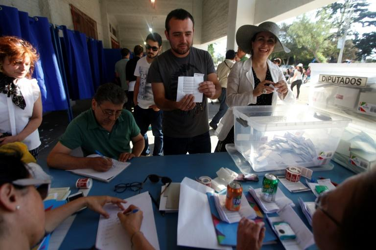 Electoral officers show ballots after closing the polls at the National Stadium in Santiago