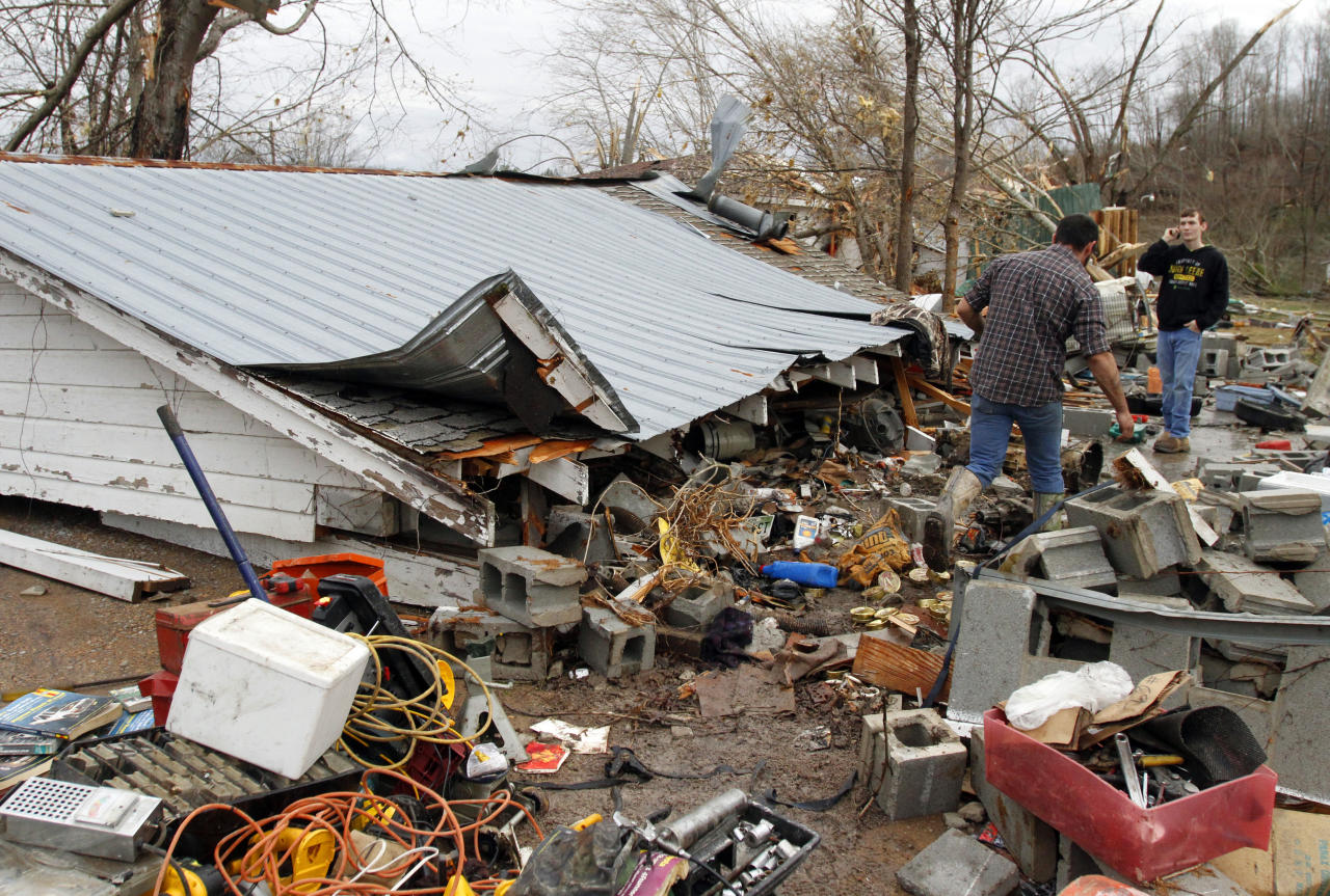 Residents search through debris after a storm ripped through Coble, Tenn. early Wednesday, Jan. 30, 2013. A large storm system packing high winds, hail and at least one tornado tore across a wide swath of the South and Midwest on Wednesday, killing one person, blacking out power to thousands and damaging homes. (AP Photo/Butch Dill)