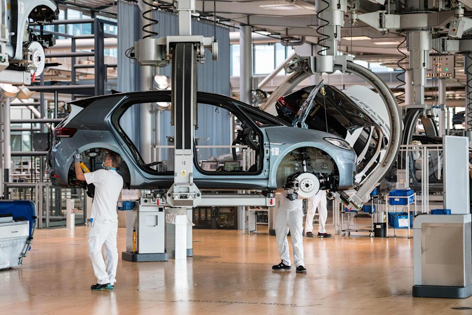 Employees work on the assembly line for the Volkswagen (VW) ID 3 electric car of German carmaker Volkswagen, at the 'Glassy Manufactory' (Glaeserne Manufaktur) production site in Dresden, eastern Germany on June 8, 2021. (Photo by JENS SCHLUETER / AFP) (Photo by JENS SCHLUETER/AFP via Getty Images)