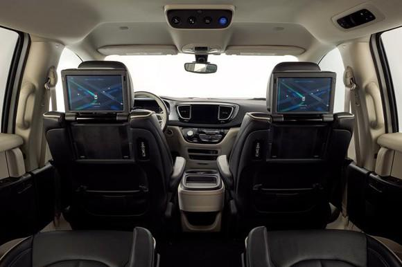 The interior view of a self-driving van, with overhead start button and screens showing route.