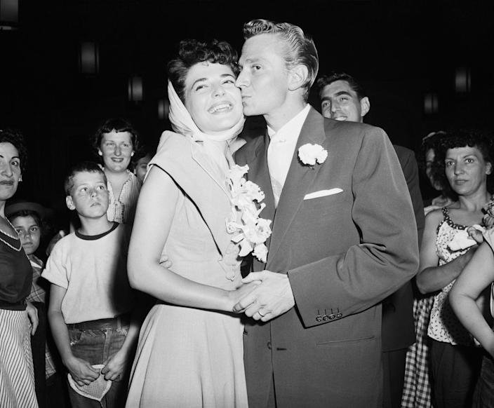 <p>Anne Bancroft tops her bridal look with a white silk headscarf and a flower corsage. The actress married Marty May in August in New York. </p>