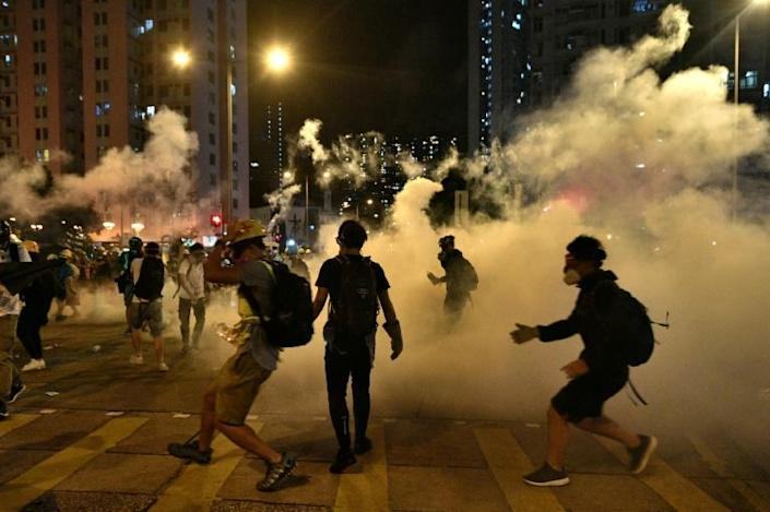 Tear gas swirls around protesters outside a police station in the Wong Tai Sin district of Hong Kong (AFP Photo/Anthony WALLACE)