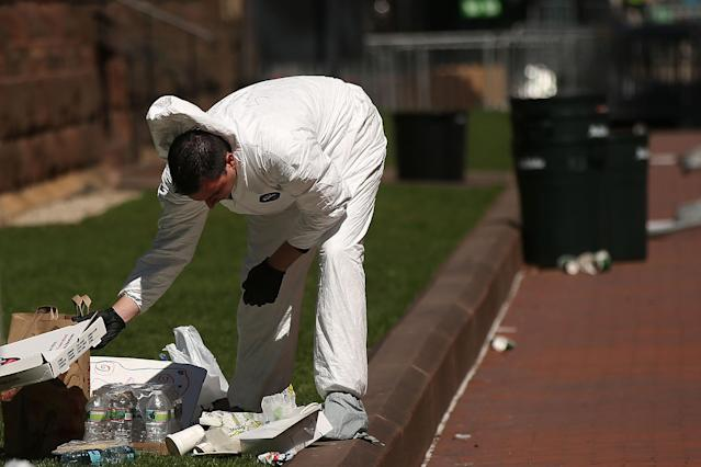 BOSTON, MA - APRIL 17: A member of the Federal Bureau of Investigation (FBI) searches for clues near the scene of twin bombings at the Boston Marathon on April 17, 2013 in Boston, Massachusetts. The explosions, which occurred near the finish line of the 116-year-old Boston race on April 15, resulted in the deaths of three people with more than 170 others injured. Security has been heightened across the nation as the search continues for the person or people behind the bombings. (Photo by Spencer Platt/Getty Images)