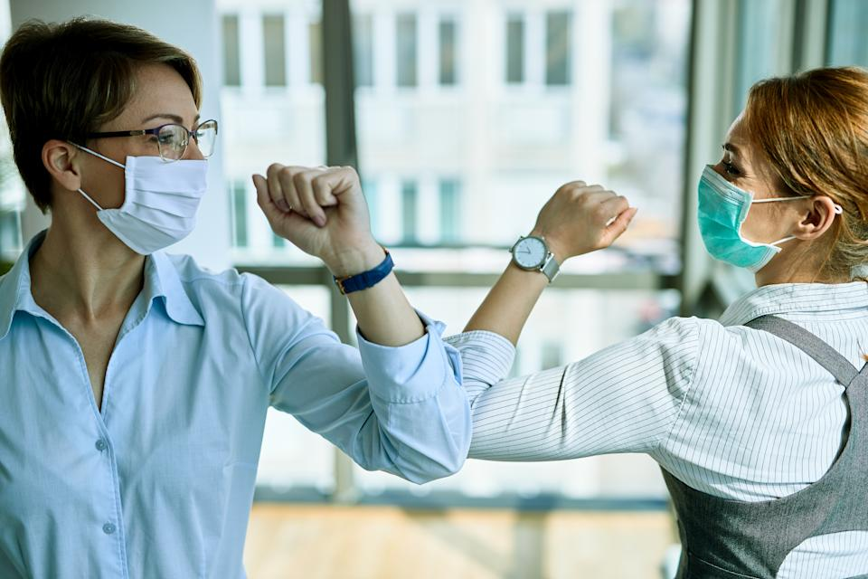 Two businesswomen elbow bumping while greeting each other in the office during COVID-19 epidemic.