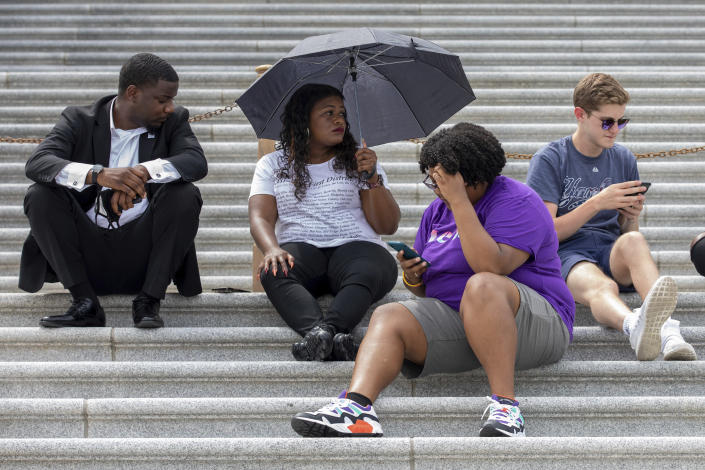 Rep. Cori Bush, D-Mo., second from left, sits with supporters advocating for reinstating the now-expired nationwide eviction moratorium sit outside of Capitol Hill in Washington on Tuesday, Aug. 3, 2021. Bush has been camped outside the U.S. Capitol in protest since the weekend. She was joined overnight Monday by Ocasio-Cortez, Rep. Jimmy Gonzalez, D-Calif., and others who gave her a brief reprieve so she could rest indoors. Bush also had a brief conversation Monday at the Capitol with Vice President Kamala Harris. (AP Photo/Amanda Andrade-Rhoades)