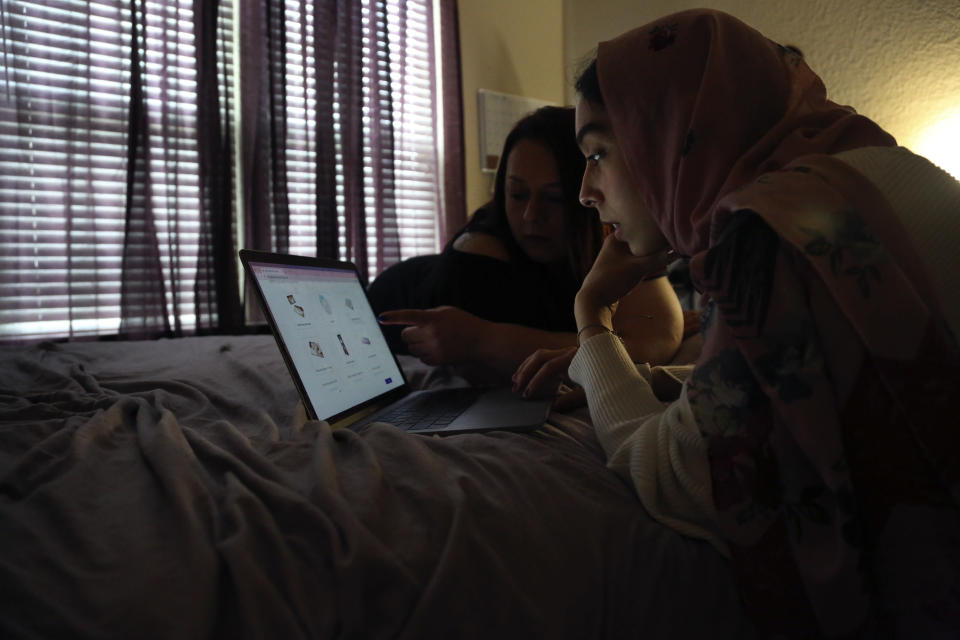 Angela Ahmed, left, and her daughter, Amirah Ahmed, 17, lay on a bed while browsing the internet on Saturday, Aug. 14, 2021, in Fredericksburg, Va. (AP Photo/Jessie Wardarski)