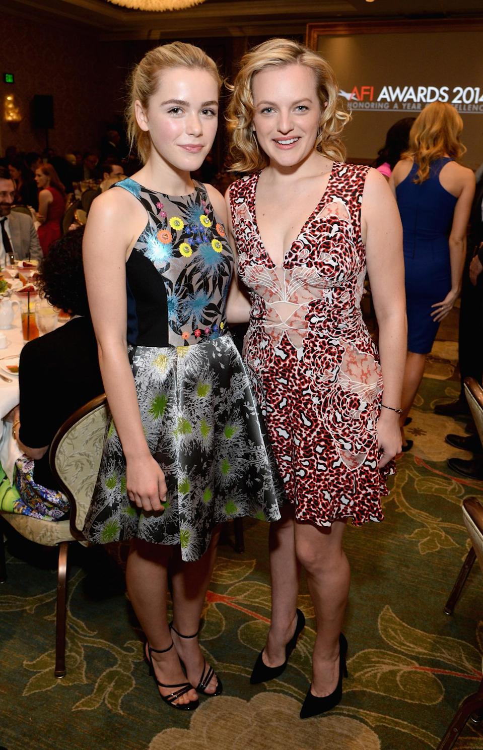 "Elizabeth Moss posed with her young ""Mad Men"" co-star. Moss wore a printed V-neck mini with coral-like printed detail in burgundy and shades of red."