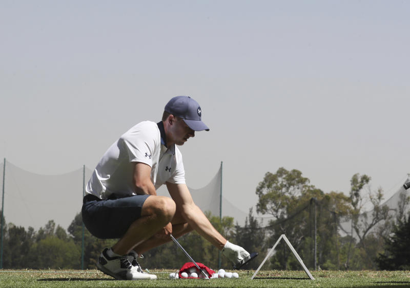 Jordan Spieth of United States checks his mobile phone in the warmup area during a practice round for the WGC-Mexico Championship golf tournament, at the Chapultepec Golf Club in Mexico City, Wednesday, Feb. 19, 2020. (AP Photo/Fernando Llano)