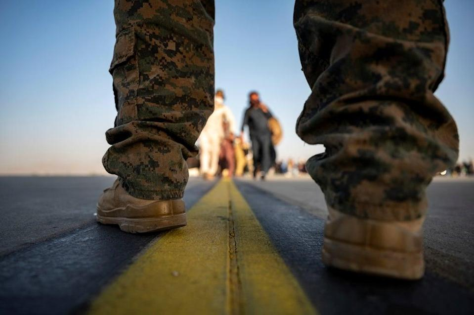 A US Marine provides security for qualified evacuees boarding a US Air Force C-17 Globemaster III in support of the noncombatant evacuation operation at Hamid Karzai International Airport in Kabul (via REUTERS)