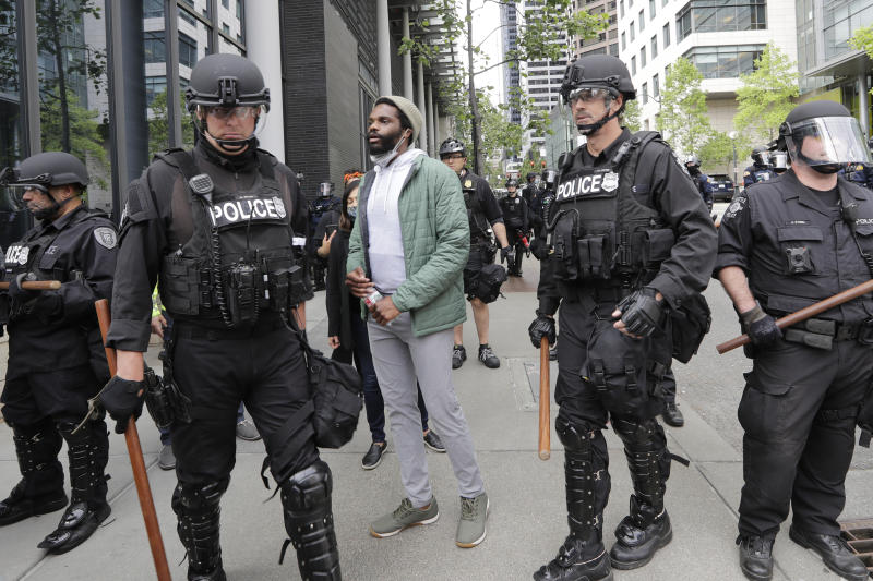 Activist David Lewis, center, walks past police officers as he heads in to Seattle City Hall to meet with the mayor Wednesday, June 3, 2020, in Seattle, following protests over the death of George Floyd, a black man who was in police custody in Minneapolis. (AP Photo/Elaine Thompson)