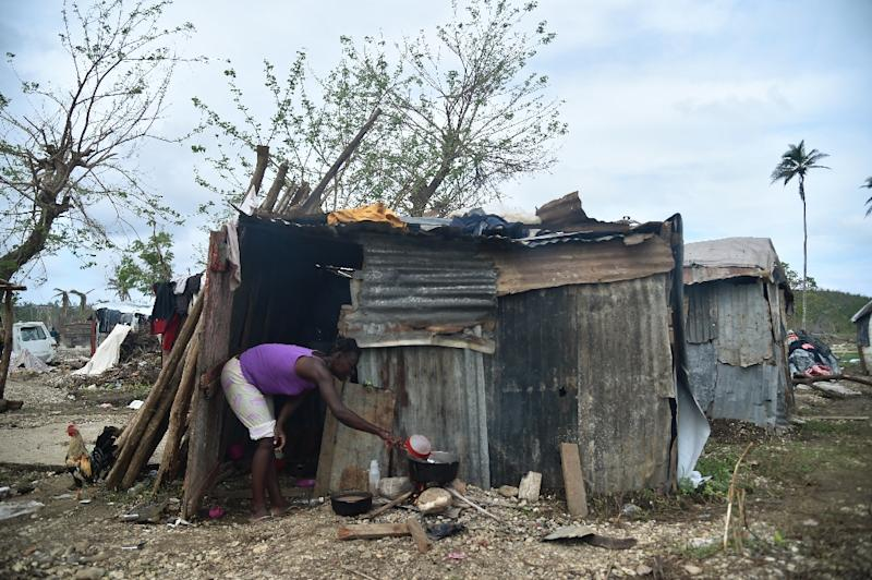 A woman prepares food on October 22, 2016 outside her home in the neighborhood of Gebeaux in the commune of Jeremie, southwestern Haiti, which was hit hard by Hurricane Matthew (AFP Photo/Hector Retamal)
