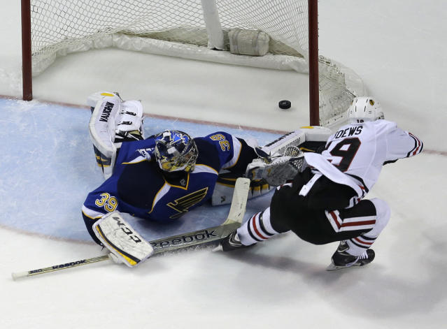 Chicago Blackhawks' Jonathan Toews, right, scores the game-winning goal past St. Louis Blues goalie Ryan Miller during overtime in Game 5 of a first-round NHL hockey playoff series Friday, April 25, 2014, in St. Louis. The Blackhawks one 3-2. (AP Photo/Jeff Roberson)