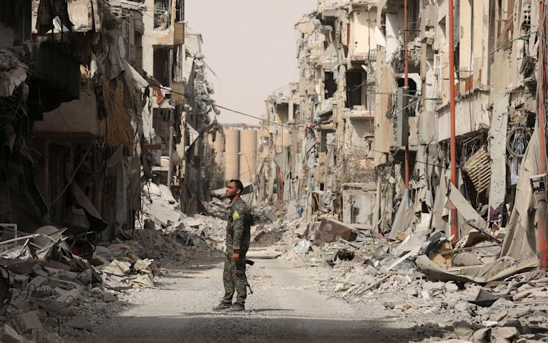 A fighter from the Syrian Democratic Forces (SDF) stands next to debris of damaged buildings in Raqqa, Syria, on Sept. 25, 2017.