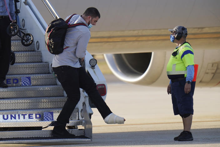 Kansas City Chiefs left tackle Eric Fisher gets off the plane with his teammates ahead of the NFL Super Bowl 55 football game against the Tampa Bay Buccaneers, Saturday, Feb. 6, 2021, in Tampa, Fla. Fisher tore his Achilles tendon during the AFC Championship against the Buffalo Bills. (AP Photo/Chris O'Meara)