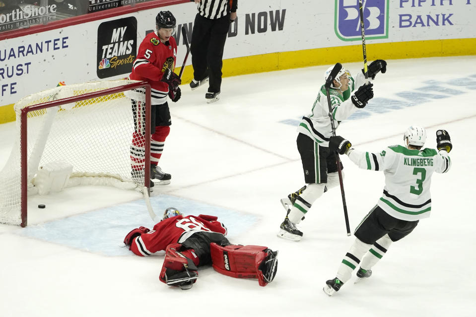 Dallas Stars' Jason Robertson (21) celebrates his winning goal with John Klingberg (3) as Chicago Blackhawks goaltender Collin Delia and Connor Murphy (5) look on during the overtime period of an NHL hockey game Monday, May 10, 2021, in Chicago. (AP Photo/Charles Rex Arbogast)