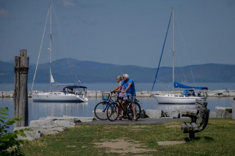 Cyclists look out at Lake Champlain in Burlington, Vermont, where the mask mandate was lifted in May