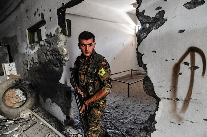 A member of the Syrian Democratic Forces inspects the municipal stadium in Raqa on October 18, 2017, after the US-backed forces retook the city from the Islamic State group (AFP Photo/BULENT KILIC)