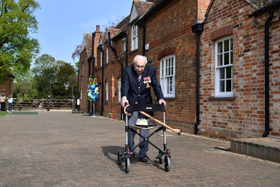 """British World War II veteran Captain Tom Moore, 99, poses with his walking frame doing a lap of his garden in the village of Marston Moretaine, 50 miles north of London, on April 16, 2020. - A 99-year-old British World War II veteran Captain Tom Moore on April 16 completed 100 laps of his garden in a fundraising challenge for healthcare staff that has """"captured the heart of the nation"""", raising more than £13 million ($16.2 million, 14.9 million euros). """"Incredible and now words fail me,"""" Captain Moore said, after finishing the laps of his 25-metre (82-foot) garden with his walking frame. (Photo by Justin TALLIS / AFP) (Photo by JUSTIN TALLIS/AFP via Getty Images)"""