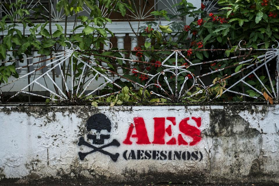 "Graffiti reads ""AES assassins"" at an abandoned house in Guayama. (Photo: Dennis Rivera Pichardo for HuffPost)"