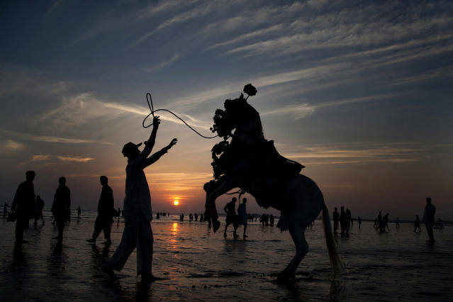 <p>Adnan Khan directs his horse to perform in an attempt to attract people visiting Clifton beach in Karachi, Pakistan, Nov. 14, 2014. Khan earns his living by providing the horse ride to customers visiting a beach. (AP Photo/Shakil Adil) </p>