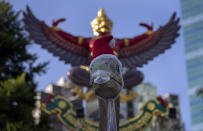 A sculpture of a dinosaurs is dressed with a Santa hat and a face mask in Bangkok, Thailand, Wednesday, Dec. 30, 2020. Officials in the Thai capital have announced new restrictions, including the closure of some entertainment facilities during the New Year's holiday, as infections continued to rise following a recent coronavirus outbreak. (AP Photo/Gemunu Amarasinghe)