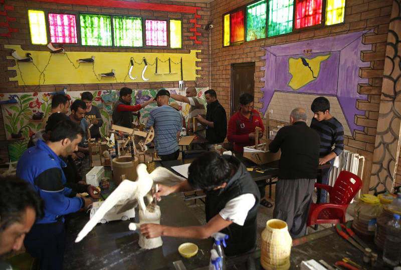 CAPTION ADDITION: ADDS DETAILS ABOUT WHICH PRISON HAD RIOTS: FILE - In this April 3, 2018, file photo, prisoners work in a handicraft workshop at a Kurdish-run prison housing former members of the Islamic State group, in Qamishli, northern Syria. A spokesman for Kurdish-led forces in northeastern Syria said Monday, March. 30, 2020, that they have put an end to riots by Islamic State militants in a prison there. The riots broke out late on Sunday in a prison in the town of Hassakeh and lasted several hours. Kurdish authorities run more than two dozen detention facilities scattered around northeastern Syria, holding about 10,000 IS fighters. (AP Photo/Hussein Malla, File)