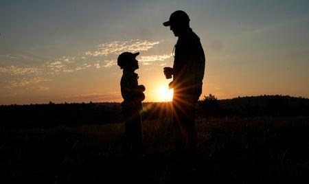 Keobs Avila (R) talks to Sielh Avila at sunrise as they wait for the solar eclipse in Guernsey, Wyoming. REUTERS/Rick Wilking